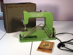 """The Elna """"Grasshopper""""(a.k.a. the Model 1) is a curious-looking machine, the first consumer free-arm machines ever made.The rather military-looking case folds open to become a large extension table. The knee-controller is integral to the machine, and folds neatly out of the way for storage. The handwheel is at bottom. Like the Necchis and Singer 201s, this machine makes a gorgeous stitch, runs very quietly, and is strong. Indeed, it is one of only two consumer machines with a true low…"""