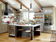 Industrial kitchen in St Helena, Napa with built-in wine fridge and pull-out seating at the island