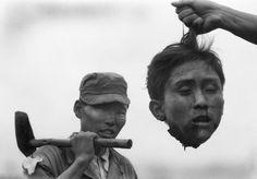 Южнокорейский полицейский держит отрубленную голову северокорейского партизана, 1952 год.