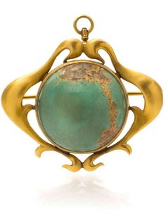 *An Art Nouveau Yellow Gold and Turquoise Brooch, containing a round cabochon cut turquoise with matrix measuring approximately 22.40 x 21.84 x 10.19 mm set within a curvilinear, openwork surround. 7.50 dwts.
