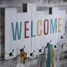 Greet your guests in a unique way with Kirkland's Welcome Wood Plank Wall Hook! Friends and family can hang their jackets, bags and purses on this fun and colorful wall piece.