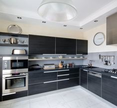 Black cabinets can create an excellent contrast to the rest of the kitchen. This home here uses white flooring and daring black cabinets for a striking and bold color scheme. See 23 Kitchens with Black Cabinets at http://www.homestratosphere.com/kitchens-black-cabinets/#utm_sguid=163048,16a5ef6f-41ec-1d47-10a5-4cf4cd6ce193 Check out 100s more kitchen designs at http://www.homestratosphere.com/category/kitchens/#utm_sguid=163048,16a5ef6f-41ec-1d47-10a5-4cf4cd6ce193