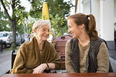 Young woman conversing with her grandmother who has dementia.