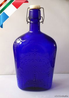 Large cobalt blue Cognac bottle with stopper. Deep blue Italian glass stopper bottle with a decorative relief of grapes and grapevines, by SoVintastic, €12.00 only