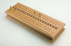 Store your cards and pegs INSIDE this hardwood double track cribbage board! This handsome cabinet card box has inlaid Italian stripes and machine turned solid metal pegs. This set can be used for a quick game if a friend stops by, a lazy day at the park or just for nice wooden home decor! Great for travel.