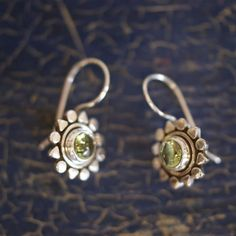 """A casual, lovely earring handmade in Taxco, Mexico. Sterling silver ear wire and the earring design is a small stone surrounded by a """"sun"""" in sterling silver. 1 pair of Peridot state of origin: Guerre"""