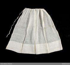 Förkläde av vit nättelduk, glesvävd tuskftad fintrådig bomullsväv. Rakt stycke av hela vådbredden med stadkanter i sidorna och 17 cm bred fåll nertill,. Rynkat i midjan mot 1 cm brett bomullsband, som vikts dubbelt som linning. Vemmenhögs härad,1840-70. Nordiska Museet, nr.  NM.0014857 B