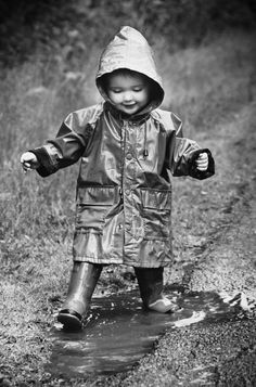 toddler in a slicker in a mud puddle, black & white B&W