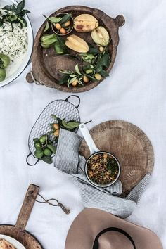 rustic wooden serving dishes, starfruit + greens on a soft white tablecloth