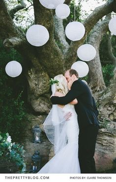 A lagoon wedding with a moody setting - fairy lights in the trees and mason jars filled with lights as beautiful decorations at this outdoor wedding | Photography by Claire Thomson