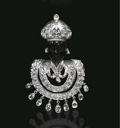Lot Description A DIAMOND AND HARDSTONE BLACKAMOOR BROOCH, BY NARDI  The carved hardstone blackamoor wearing a rose-cut diamond and etched white gold turban, enhanced by a central briolette-cut diamond, with diamond collet ear pendants and a tunic of similar design, suspending a briolette-cut diamond fringe, mounted in 18k white gold Signed Nardi