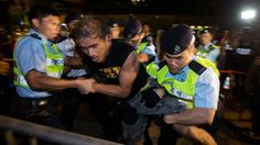 A pro-democracy activist is detained by the police during a confrontation outside the hotel where China's National People's Congress (NPC) Standing Committee Deputy General Secretary Li Fei is staying, in Hong Kong.(Reuters / Tyrone Siu )