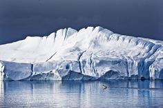 Huge iceberg on still waters. You cannot avoid feeling small in those magnificent surroundings. Ilulissat ice-fjord with small boat. Photo by Uri Golman
