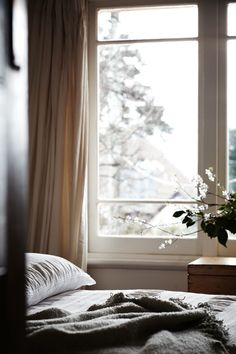 charcoal throw + wooden trunk near the window.