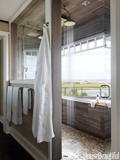 In a Shingle Style beach house decorated by Rob Southern, a six-by-nine-foot master bathroom shower has two Waterworks Easton Classic showerheads and stunning bay views. An interior window opens up the whole bathroom to sunlight and the views.
