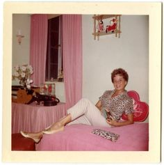 1960s found photo woman in bedroom pink curtains bedspread leopard shirt top blouse white pencil pants hairstyle shoes early 60s to late 50s color vintage fashion style