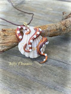 Take his seashell...if you dare!  Seashell and tentacles 100% handcrafted in polymer clay, with gold tone bail and suspended on brown braiding cord with adjustable knots. Cord adjusts up to a 25 circumference.  Pendant measures 1.5 tall and 1.25 wide.