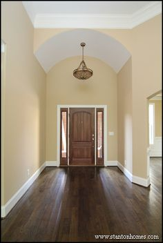 One story foyer with white barrel vault ceiling and dark hardwood floors.