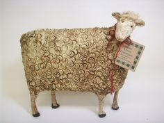 This very Primitive Sheep is made of a papier mache/sawdust mixture and some very heavy wire. She stands 9 inches high and is 10 inches long and about 2 inches wide. She has been painted, stained and sealed.    She wears a little rustic red jute bow around her neck.