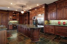 """GRANITE KITCHEN - 16X20. Custom stained-wood cabinetry; slab granite counters with bullnose edging; self-cleaning double ovens; 48"""" French door refrigerator; circular snack table at end of large island. Central vacuum system plus a full-house water filter system."""
