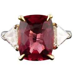 Padparadscha sapphire flanked by trilliant cut diamonds. Set in yellow gold and platinum.