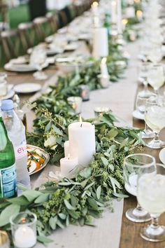 Rustic Table Topped with Fresh Garland & Candles | Photography: Stacy Newgent. Read More: http://www.insideweddings.com/weddings/rustic-barn-wedding-tented-reception-on-family-farm-in-ohio/690/