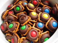 Pretzel, Hershey Kiss, M & M Bites. 1. Place pretzel squares on baking sheet, & top each one with a Hershey Kiss. 2. Bake for 3 minutes in 200 degree oven. 3. Press an M & M into center of each Kiss. Refrigerate.