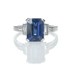 Stock Number: VR507-05 Art Deco platinum ring with sapphire. An Emerald cut sapphire weighing 2.11 cts is set low in a four prong basket with four diamond baguettes set both north/south and east/west in the shoulders (HI/VS with a total weight .35 cts). A beautiful and elegant design, the sapphire is new to the c. 1930 setting. Platinum.  $4,975