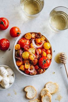Honey Roasted Tomatoes | If you've been buying pints of cherry tomatoes at the farmers market, you know how delicious they are this time of year.  All you have to do is toss the tomatoes with olive oil, honey, and sliced red onion; bake them until they're soft and bursting; and then serve them in a bowl with fresh mozzarella, thyme, salt, and pepper. Roasting brings out the natural sweetness of the tomatoes, and the honey adds a deep caramel note.