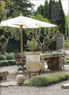 Concrete table. Grassy flowers. Pebbles. Stone backyard. Large pot.