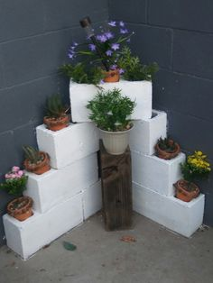 Summer style!! Painted cinder block planter - corner planter for a patio, terrace or deck! Just check and create good drainage for both the plants -- and to protect the patio too! Maybe add outdoor lights!