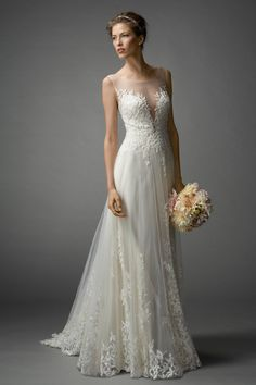 Beaded Leaf Embroidery on Illusion Tulle and a plunging neckline on Illusion. Pearl buttons down the back. Sweep train.Watters Brides Lalai Gown