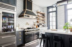 Alison Cayne's kitchen in Manhattan's West Village combines so many of our favorite kitchen trends of the year: white subway tile laid with dark grout, brass hardware and fixtures, open shelving, and dark cabinetry paired with white countertops.