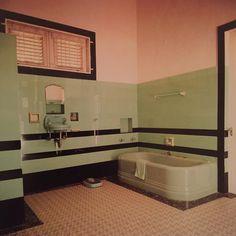 Een badkamer uitgevoerd in de voor de jaren twintig typerende art deco-stijl: zeegroen sanitair en zeegroene tegels met strakke zwarte sierranden.