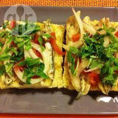 De topping voor deze zuid-Italiaanse bruschetta is een combinatie van gemarineerde ansjovis, kerstomaten, rode ui, rucola, oregano en gedroogde chilivlokken.