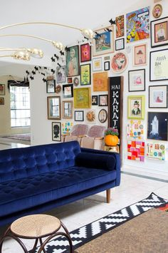 Sophisticated design with playful details. Eclectic pictures, blue velvet couch, brass fixtures, and theater seats.