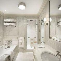 Mark Hampton LLC - bathrooms - marble bathrooms, marble bathroom ideas, marble clad bathroom, marble paneling, marble paneled bathroom, marble bathroom paneling, train rack, paneled bathtub, wall mounted tub filler, marble wainscoting, walk in shower, rain shower head, teak shower bench, inset mirror, water closet, mirrored bathroom door, mirrored water closet door, extra long sink vanity, oval sink, white marble countertops, inset vanity mirror,
