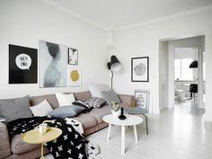 salon scandinave blanc aménagé avec un canapé marron clair, trois tables basses rondes et beaucoup de coussins en blanc et gris