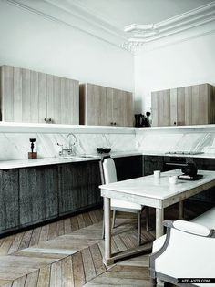 Love the different textures of wood combined with the traditional molding - Apartment of Gilles & Boissier