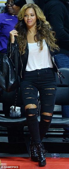 Stylish as ever: Beyonce donned a pair of super-ripped black skinny jeans with towering chunky ankle boots for the evening of sport, topped of with a simple white cami and leather jacket