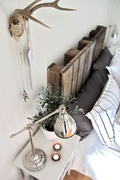 easy DIY pallet headboard. Rustic, country, nature, woodsy feel in the bedroom. With a few decor items to tie in such as antlers, and a plant at bedside.