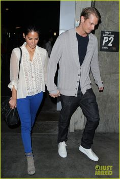 : Photo Olivia Munn holds hands with her boyfriend Joel Kinnaman as the two leave ArcLight Cinemas on Thursday (August in Hollywood, Calif. The cute couple tried… White Top And Blue Jeans, White Tops, Jean Outfits, Cool Outfits, Joel Kinnaman, Blue Dress Pants, Grey Booties, Olivia Munn, Office Looks