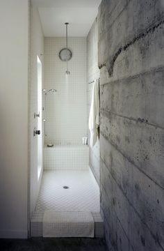 Board-formed concrete bath wall Love the open, tiled, defined space. LOVE that there is no glass/curtain. Love the built in bench + gorgeous light.