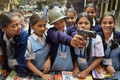 A girl takes aim with a gun at a workshop for showcasing arms and equipments used by the police, organised by Naupada Police station in Thane.