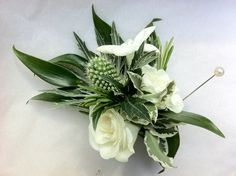 Neutral corsage of ivory spray roses, eryngium thistle, stephanotis, variegated pitto, rosemary & soft ruscus. Attached with a corsage magnet and pearl-headed pin for extra securing.