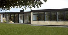 Lysebrunt parcelhus med gulv-til-loft-vinduer påført i sorte rammer