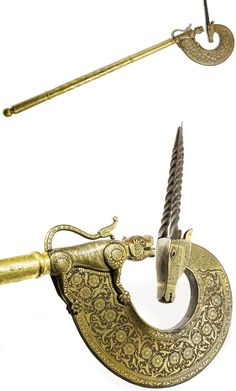 Indian (Mughal) tabar (axe) in the form of an ibex and tiger,18th century, the steel crescent shaped blade emanating from a tiger and terminating in an ibex head with fine damascened decoration, the gilt handle with pierced and incised floral design 66cm. length.