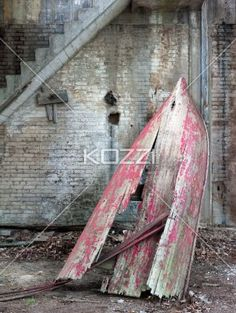 old wooden boat by bricked wall and staircase. - Old wooden boat by bricked wall and concrete staircase.