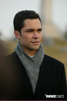 Medium shot of Danny Pino as Scott wearing coat and scarf. (Photo by Carin Baer/Warner Bros./Getty Images)