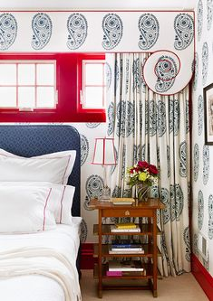 This blue and white paisley bedroom with a pop of red lacquer paint designed by…